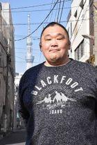 引退した1月末、伊勢ケ浜部屋の前に立つ棟方さん。後方には東京スカイツリーがそびえる=東京・江東区