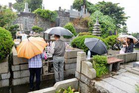 悪天候にもかかわらず多くの花が飾られた墓前でお参りする熱心なファンら=24日午後2時ごろ、横浜市港南区の日野公園墓地
