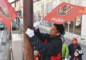 サポーターらと名古屋グランパスの旗を街頭に取り付ける秋山選手=名古屋市千種区今池で