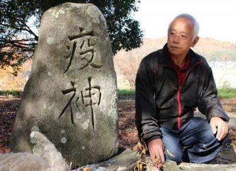 造山古墳にある「疫神」の文字が刻まれた石碑。疫病封じを願って建てられたとみられる。右は定広会長