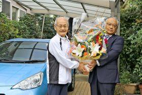 お祝いの花を受け取る吉野さん(左)=9日、藤沢市内(横浜トヨペット提供)