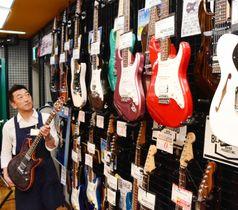 中信地方で製造したギターを紹介する太田さん。祭りで展示する品もある