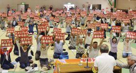 陸上自衛隊が導入する輸送機オスプレイの佐賀空港配備計画に反対する決起集会で「オスプレイ来るな!」と記したカードを掲げる参加者=26日午後、佐賀市