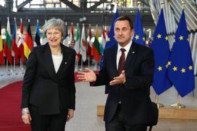 13日、ブリュッセルのEU首脳会議会場でルクセンブルクのベッテル首相(右)の出迎えを受けるメイ英首相(ゲッティ=共同)