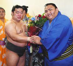 最後の土俵を終え、御嶽海(右)から花束を贈られ目頭を熱くする出羽疾風=両国国技館で