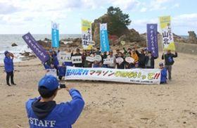 笹川流れマラソンへの参加を呼び掛ける写真を撮影する住民ら=村上市