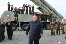 24日、「ロケット砲」の試射を指導する北朝鮮の金正恩朝鮮労働党委員長(中央)(朝鮮中央通信=共同)