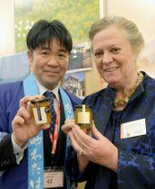 愛媛県産のかんきつ類を使ったマーマレードを手にする大城一郎八幡浜市長(左)と、英国の品評会の主催者ジェーン・ヘーゼル・マコッシュさん=17日、ロンドンの日本大使館(共同)