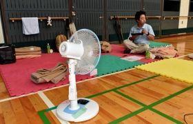 空調設備のない体育館で、扇風機で暑さをしのぐ避難者=11日午前、神戸市灘区青谷町1