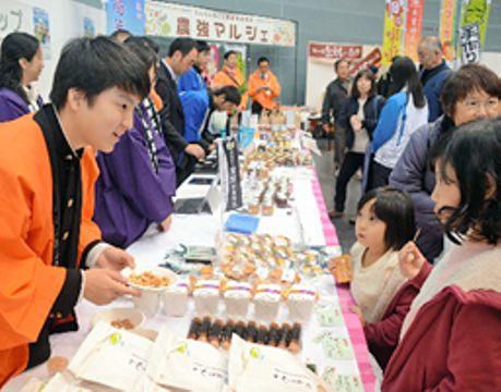 実習で作った農産加工品の試食を勧める高校生(左)
