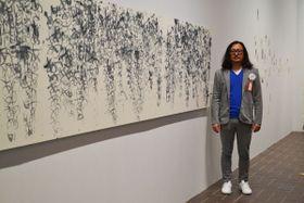 【横5メートルにわたる大作「雨を聴く」と菊山氏=東京都台東区上野公園の東京都美術館で】