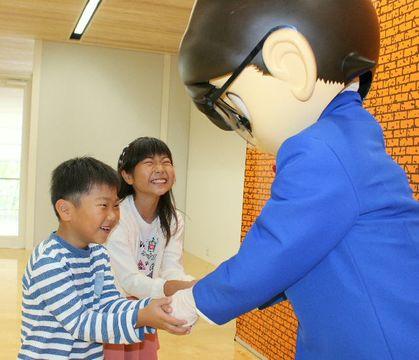 コナンと握手して喜ぶ子どもたち=21日、大分市の県立美術館