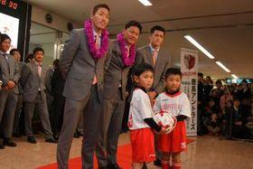 宮崎市の園児と記念撮影する(手前左から)昌子、大岩監督、植田=宮崎空港