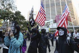 「五大要求」を掲げる民主派団体の呼び掛けに応じ、星条旗などを手に集まるデモ参加者=8日、香港(共同)