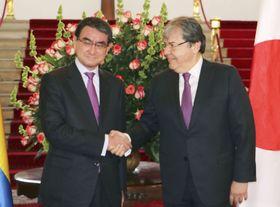 会談前に握手する河野外相(左)とコロンビアのトルヒジョ外相=16日、ボゴタ(共同)