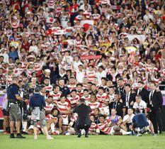スコットランドを破って初の8強入りを果たし、笑顔で記念写真に納まる日本フィフティーン=日産スタジアム