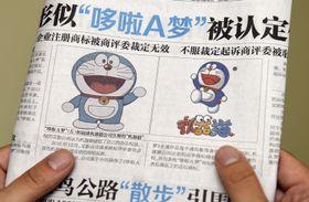 2日、中国紙に掲載された「ドラえもん」(左)と福建省のスポーツ用品企業が商標登録していたキャラクター(共同)