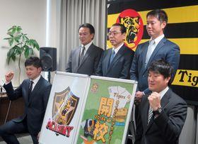 「タイガースアカデミー」の開校を発表し、写真に納まる阪神の球団幹部ら=18日午後、兵庫県西宮市