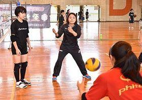 中学生に指導するバレーボール選手の座安琴希さん(中央)=5月25日、うるま市の具志川東中学校
