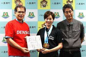 新垣安弘町長(左)に色紙を渡す伊集南選手と父の守良さん=6月27日、八重瀬町役場