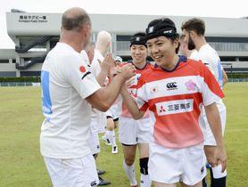 「ブラインドラグビー」の試合を終え、イングランド代表がつくった花道を笑顔で引き揚げる日本代表=14日午後、埼玉県熊谷市