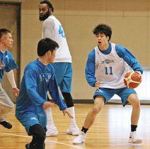 試合形式の練習でボールを運ぶ佐藤選手(右)=大津市で