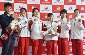 世界選手権の出発セレモニーで、ポーズをとる寺本明日香(右から3人目)ら体操女子代表=23日、成田空港