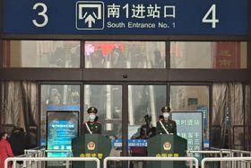 22日、中国・武漢市の鉄道駅でマスクをする武装警察(ゲッティ=共同)