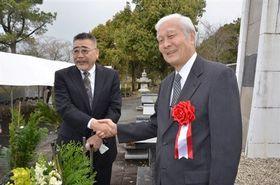 西南戦争の慰霊塔の前で握手する西郷隆文さん(左)と谷忠昭さん=熊本市北区