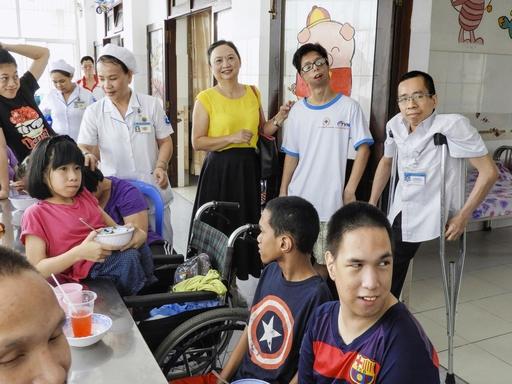 トゥーズー病院のリハビリ施設「平和村」。枯れ葉剤の影響による障害児たちが、女性医師グエン・ティ・フオン・タン(中央)の元に集まって来た。右端は病院職員として働くグエン・ドク=19年9月、ベトナム・ホーチミン(撮影・石川文洋、共同)