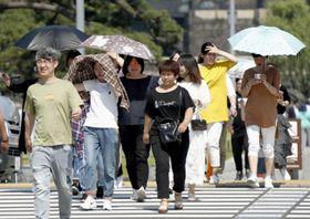 強い日差しの中、日傘を差して皇居付近を歩く人たち=27日午前