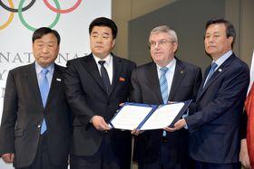 4者会談の合意書を手にする(左から)李熙範・平昌五輪大会組織委員会会長、金日国・北朝鮮オリンピック委員会委員長、IOCのバッハ会長、韓国の都鍾煥・文化体育観光相=20日、ローザンヌ(共同)