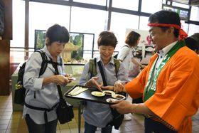 餅を振る舞い県南地域の魅力をアピールする関係者(右)