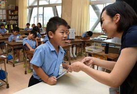担任の教諭から通知表を受け取る児童=岡山市・芳泉小
