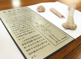 牛川人骨を「化石人骨」と説明していた地元市民館の当時のプレート。奥は発見された骨片のレプリカ=愛知県豊橋市牛川町で