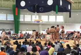 大相撲沖縄場所が開幕し、取り組み前の稽古をする力士ら=14日午前、うるま市の具志川ドーム