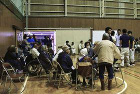 避難所となった岩船中学校の体育館に集まってきた人たち=19日午前0時12分、新潟県村上市