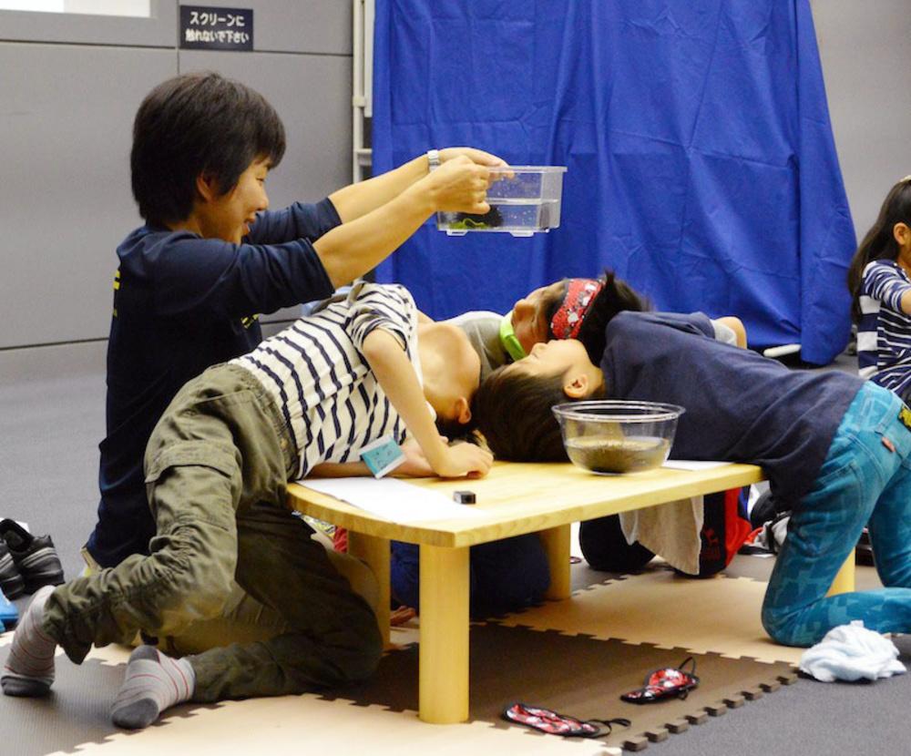 「海のあそびや」プログラムの一場面。天野未知さんの持つ水槽を下からのぞく子どもたち=東京・葛西臨海水族園
