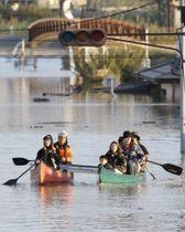 台風19号による大雨で千曲川が決壊し、ボートで救助される人たち=10月13日午後4時45分、長野市豊野町豊野