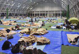 長野市の避難所で、寒さに耐えながら横になる人たち=13日夜
