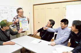 完成したまつりのポスターをチェックする実行委のメンバー=18日、静岡市清水区由比北田