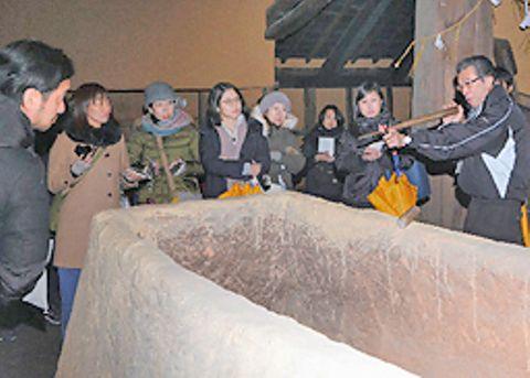 朝日光男施設長(右端)の説明を聴きながら菅谷たたら高殿の炉を見学する参加者=雲南市吉田町吉田