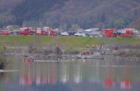 救助活動を行う岡山市消防局の消防隊員ら=24日、岡山市北区玉柏の旭川