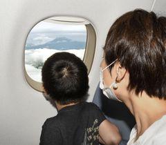 フジドリームエアラインズが開催した遊覧飛行で、小型ジェット機内から富士山を眺める乗客=20日午後
