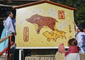 来年の干支「亥」にちなんだイノシシの親子に掛け替えられた、道明寺天満宮のジャンボ絵馬=13日午後、大阪府藤井寺市