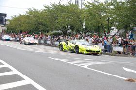 【公道をパレード走行するレーシングカー=鈴鹿市庄野羽山4丁目のイオンモール鈴鹿前で】