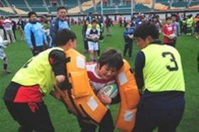 ヤマハ発動機の選手の指導を受け、勢いよく体当たりする子ども=17日午前、袋井市愛野のエコパスタジアム