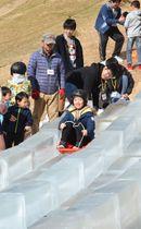 氷の滑り台を楽しむ子どもら=高松市牟礼町、石匠の里公園