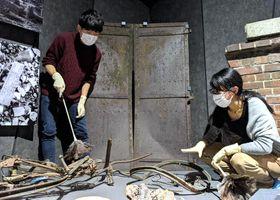 土肥学芸員(右)の指導を受けながら、被爆した自転車のほこりを慎重に払う丸さん