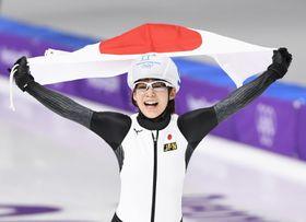 平昌冬季五輪のスピードスケート女子マススタートで金メダルを獲得し、笑顔で日の丸を掲げる高木菜那=24日、韓国・江陵(共同)